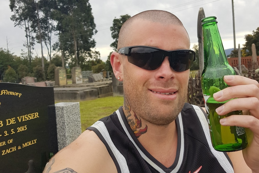 A man wearing sunglasses and holding up a bottle of beer.