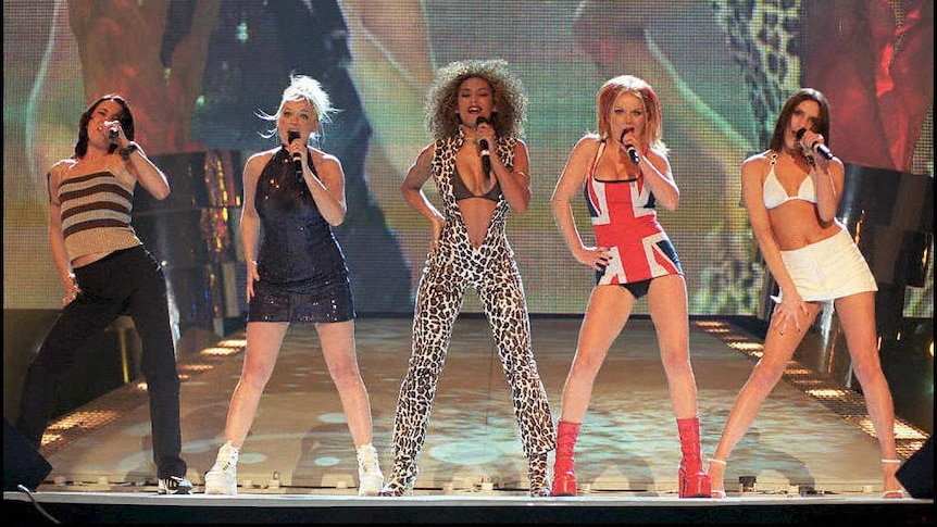 Mel C (Sporty), Emma (Baby), Mel B (Scary), Geri (Ginger) and Victoria (Posh) strike power stances while performing on stage.