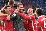 Liverpol players swarm around Alisson, who is wearing his goalkeeper kit, in wild celebration