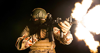 A blast of fire shoots out of a soldier's rifle.