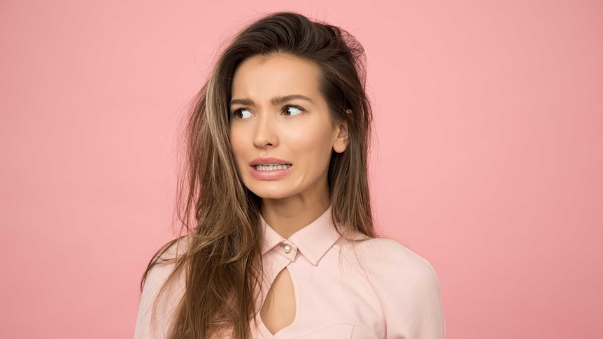 Woman looking anxious and confused with a pink background