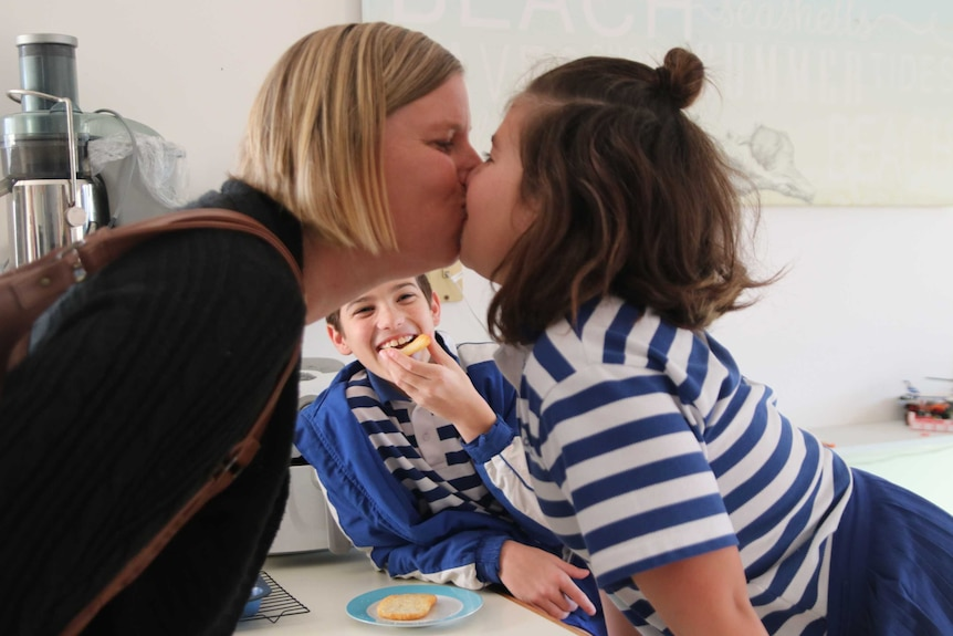 Kate Manson kisses goodbye her daughter Kayla while Noah laughs in the background, they live in a multigenerational household.