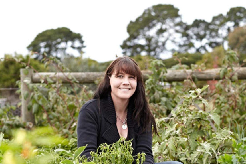 A woman with dark hair crouches in a large vegetable garden, smiling at the camera.
