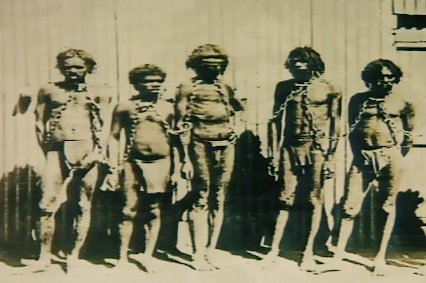 A historic photo of Aboriginal men and boys in chains.