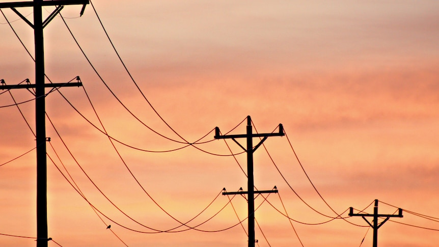 Electricity poles are silhouetted against a pinky-orange sunset sky.
