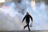 A protester escapes a cloud of tear gas during clashes with security forces near the Interior Ministry in Cairo.