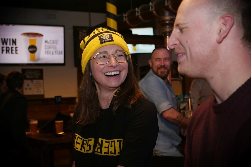 Kim and Dane laugh while watching the Collingwood vs Richmond game at the pub