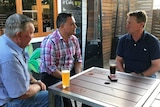 Three men sit at a table at a pub