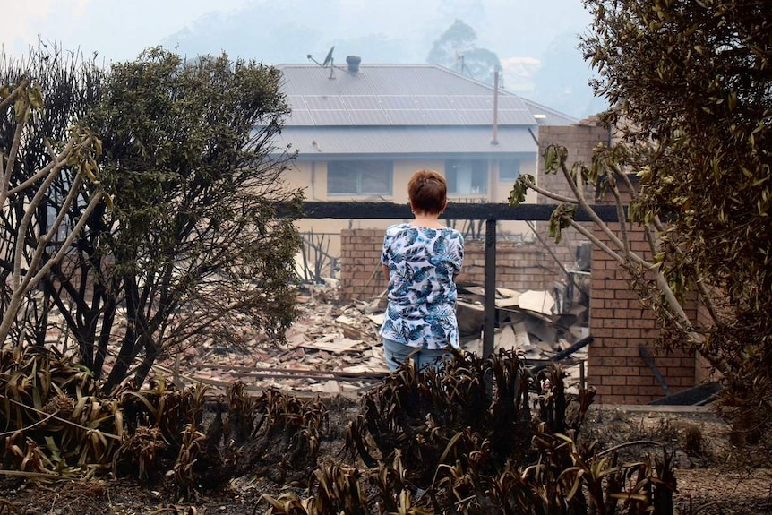A woman looks at ruins of home