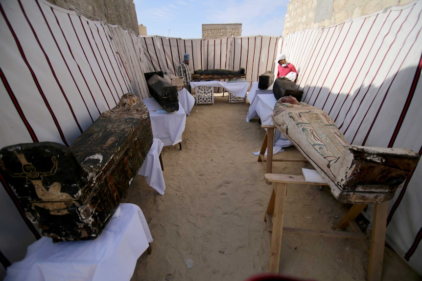Coffins on tables inside ancient Egyptian ruins