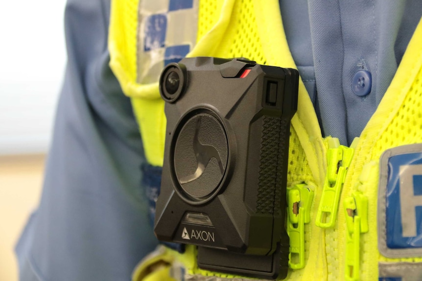A black compact camera worn by a policeman