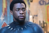 Chadwick Boseman dressed as Black Panther standing in front of a camera.