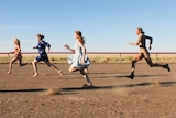 Five women running on a dusty horse racing track.