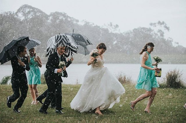 A bridal covers tries to seek cover under umbrellas in pouring
