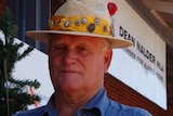 Peter Martin stands in front of the Christmas tree outside Dean Nalder's office.