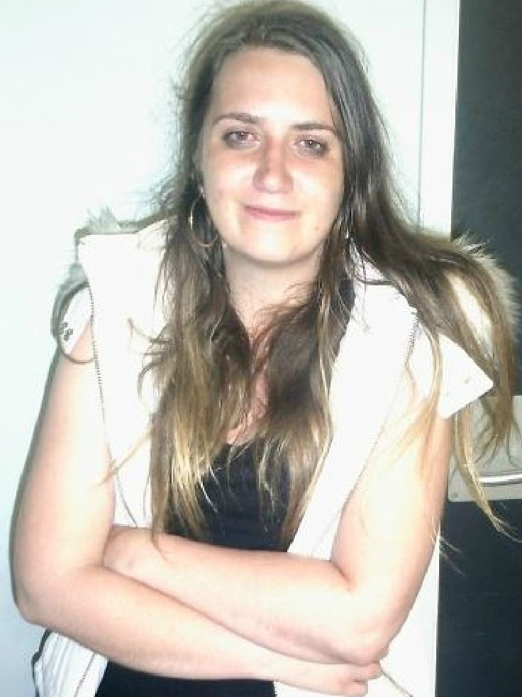 A young woman with long brown hair poses for a photo with her arms crossed.
