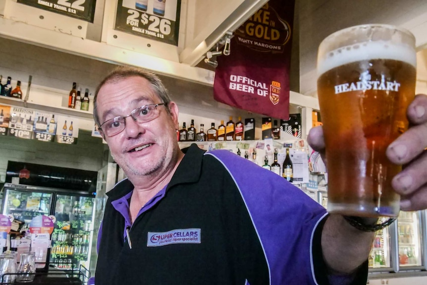 A man stands in a pub holding a beer towards the camera.