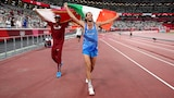 Two smiling athletes walk together on the Olympic track in Tokyo, one carrying the Qatar flag, the other the Italian.