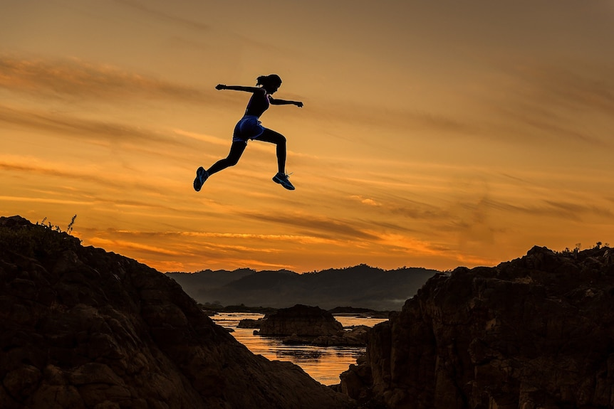 A woman leaping in the air silhouetted against a sunset