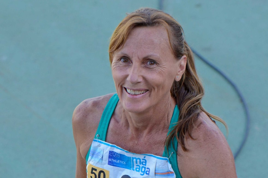 A woman in athletic clothing smiles on track.