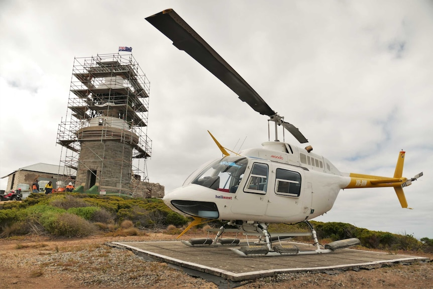 A helicopter sits on a helipad in front of a lighthouse on an island.