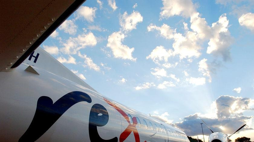 """The fuselage of a white, propeller-driven aeroplane. It reads """"Rex""""."""