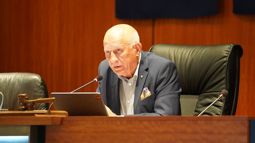 An older man in a suit sits in council chambers.