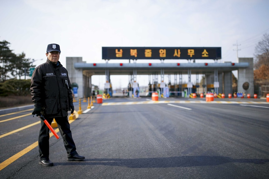 A man with a baton stands at a checkpoint on the Korean border