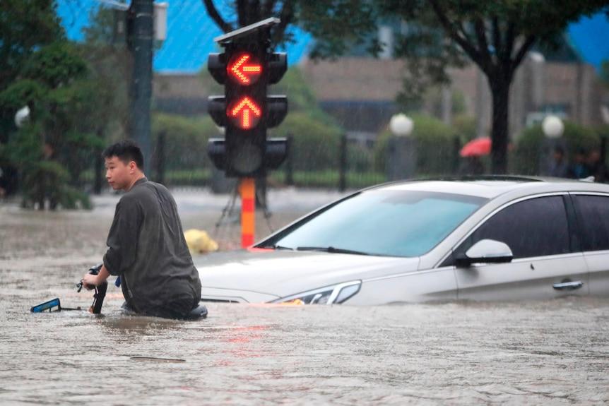 Mężczyzna jedzie na rowerze przez zalane skrzyżowanie.