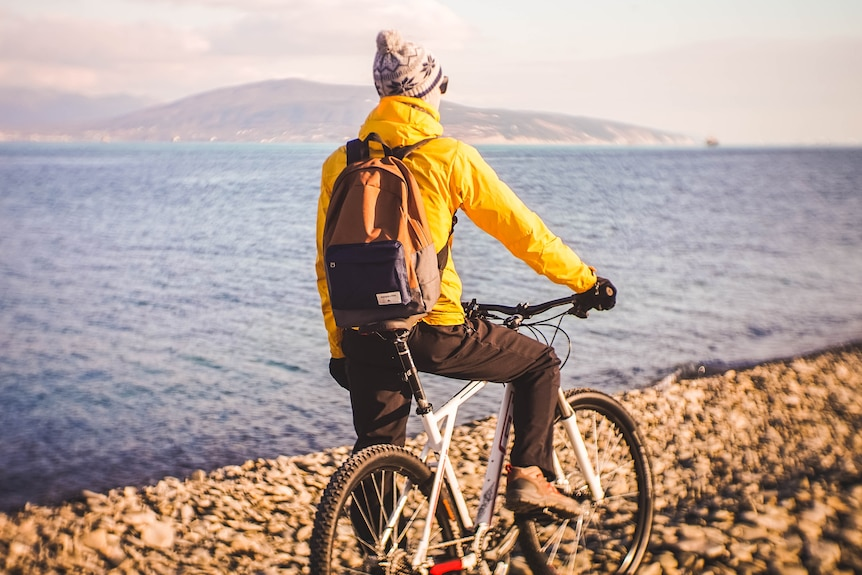 Man with a bike overlooking a body of water