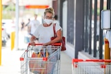 A woman wearing a white shirt and white face mask wheeling a trolley into a supermarket.
