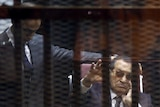 Ousted Egyptian president Hosni Mubarak (right) waves from the defendant's cage