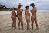 Naked people lined up from  back on the beach