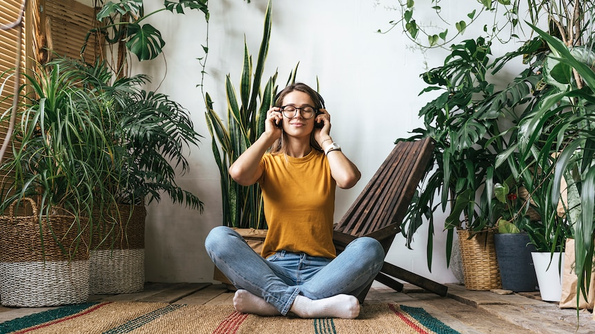 Young woman sits cross-legged in a plant-filled apartment and listens to music with a serene expression.