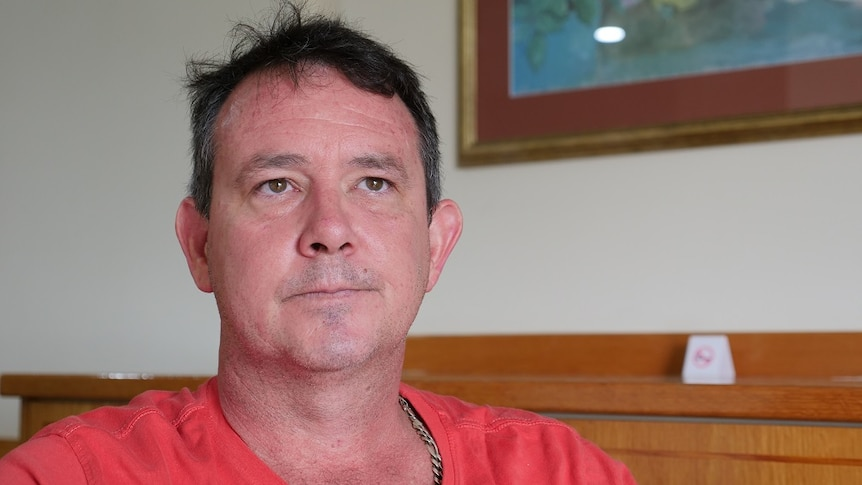 Close up of middle-aged man looking concerned, wearing red t-shirt.