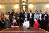 Woman in a white pattern jacket sitting in a room in parliament with a row of people behind her.