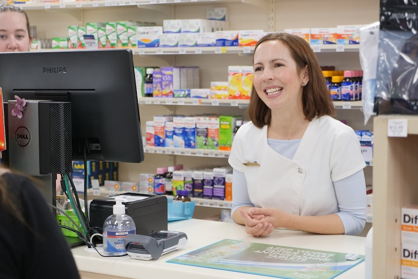 A pharmacist leans over a counter in a store to talk to a customer.