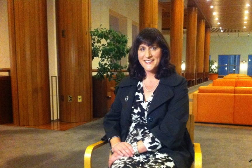 Catherine Ordway sits on a chair and looks at the camera.