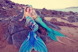 Professional mermaid performers Amelia Lassetter and Jessica Bell recline on rocks.