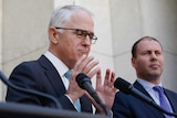 Malcolm Turnbull gestures with both hands, Josh Frdyenberg stands behind him.