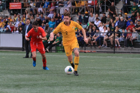 A footballer in a yellow kit running with a football at his feet.
