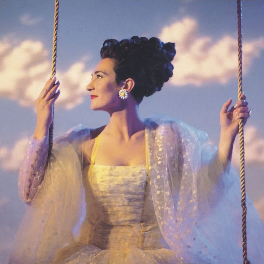 kd lang sits on a swing wearing a white formal dress, hair styled up and back (may be wig). Blue sky and clouds in background.