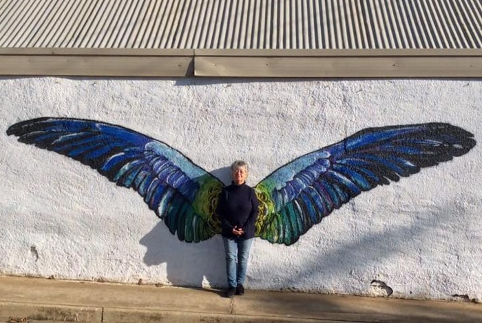 A woman is standing in front of a mural of blue and green wings, painted on a white wall.