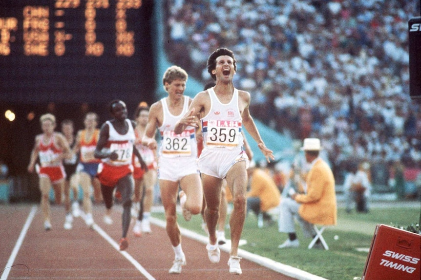 A young Sebastian Coe yells as he runs ahead of others on a running track in front of a large audience.