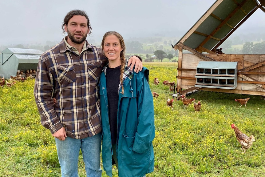 Egg producers standing in field with portable shed