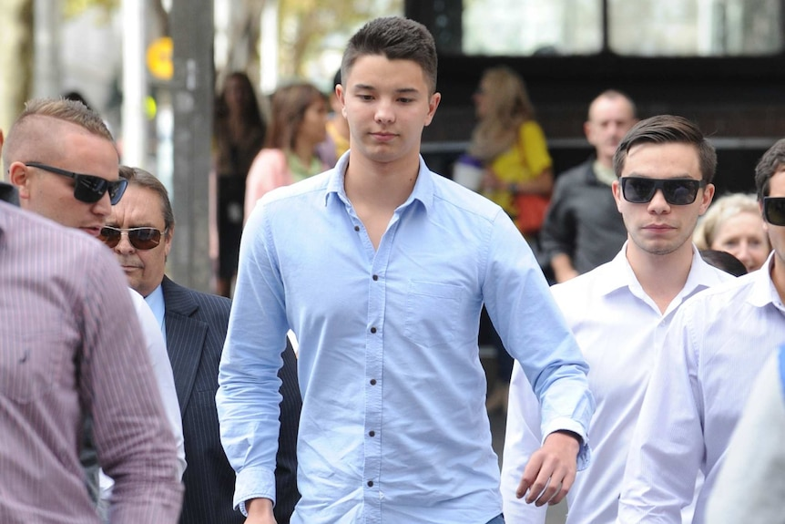 Liam Knight (C) arrives at the Downing Centre court