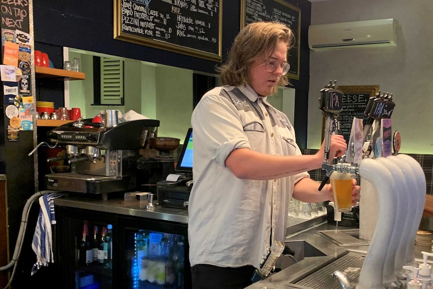A blonde man wearing glasses pours a beer into a glass from a beer tap