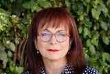 An older, bespectacled woman with dyed red hair looks candidly at the camera.