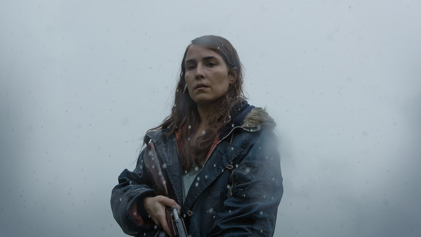 Woman with wet dark hair, wearing a navy hooded jacket and holding a shotgun is shrouded in fog and rain.