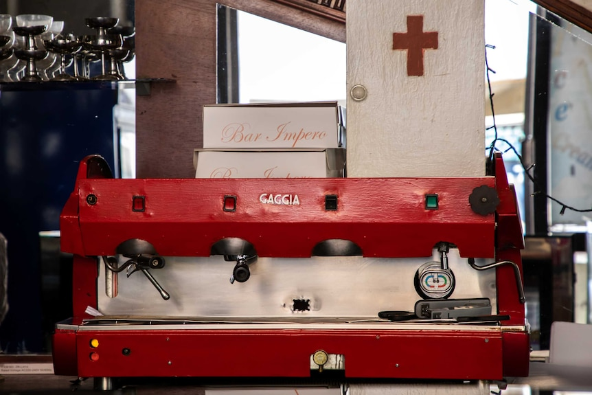 A red espresso machine sits on a bench